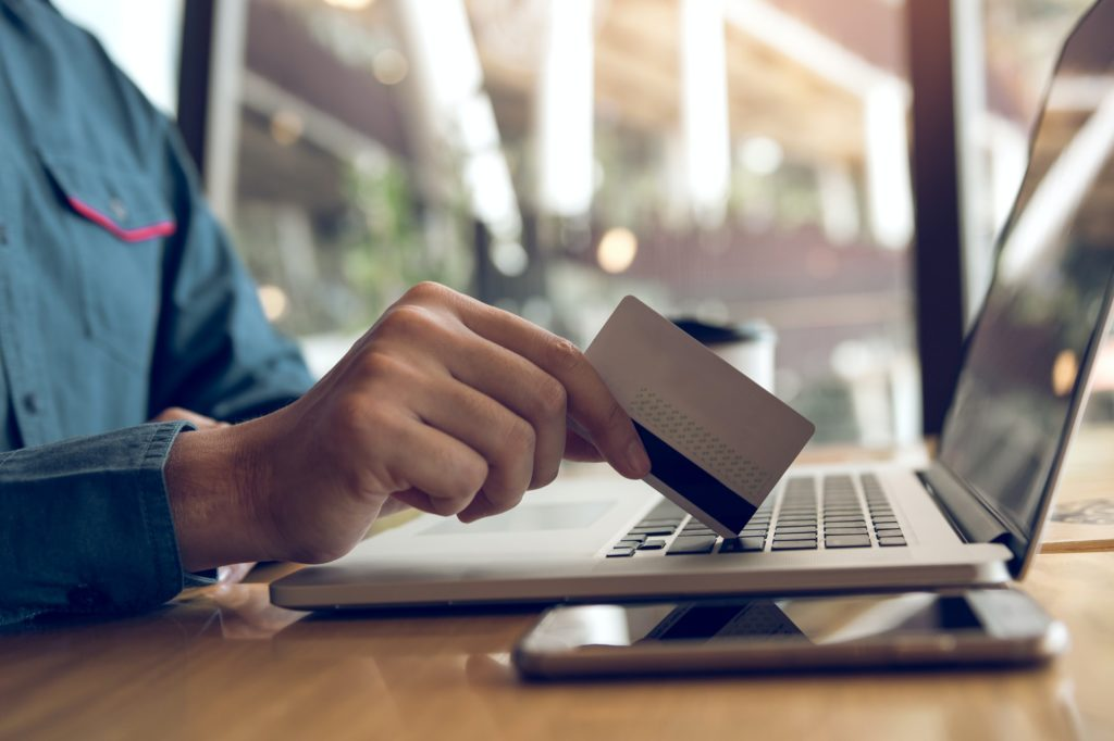 Man using credit card with shopping online concept at cafe.